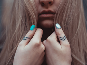Girl with detailed tattoos on her thumbs