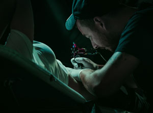 Tattoo artist tattooing a customer.