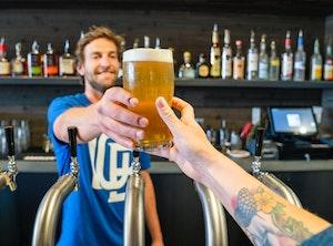 Bartender serving beer to tattooed man.
