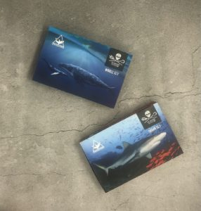 Les sets d'encres Sea Shepherd Tattoo Whale & Shark sur fond gris.