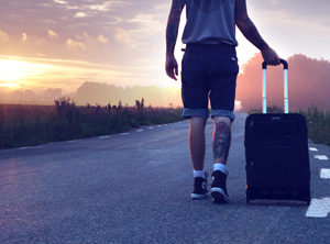 Tattooed man travelling with suitcase