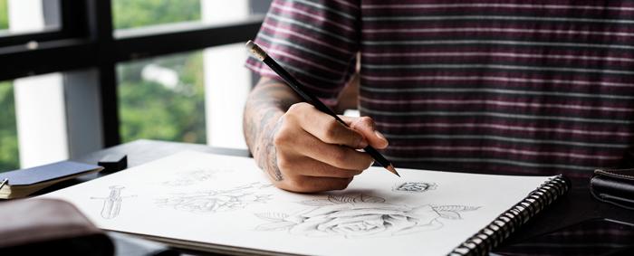 Homme dessinant des modèles de tatouage à l'aide d'un crayon et de papier