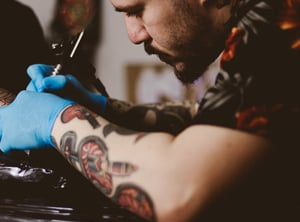 Tattooist with moustache working on a tattoo